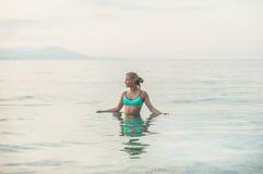 站立在海的蓝色泳装的少妇在阿拉尼亚 免版税库存照片