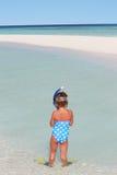 站立在海滩佩带的废气管和鸭脚板的女孩 图库摄影