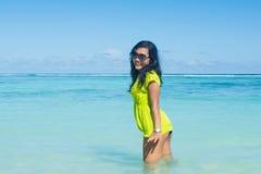 站立在海洋和做性感的姿势的年轻美丽的亚裔女孩画象  免版税库存照片