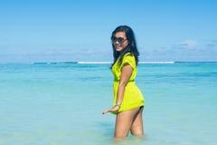 站立在海洋和做性感的姿势的年轻美丽的亚裔微笑的女孩画象  库存照片