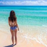 站立在海滩和看t的泳装的少妇 免版税库存图片
