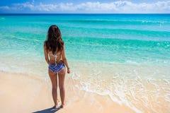 站立在海滩和看t的泳装的少妇 图库摄影