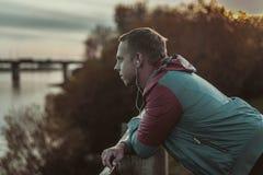 站立在海滩和神色入距离河到桥梁,听的音乐的可爱的年轻运动人 免版税库存照片