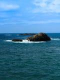 站立在海洋外面的岩石 免版税库存照片