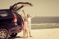 站立在海滩的一辆汽车附近的两个姐妹 免版税图库摄影