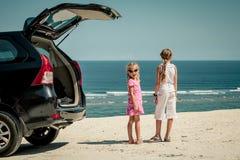 站立在海滩的一辆汽车附近的两个姐妹 图库摄影