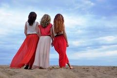 站立在海滩的一件长的礼服的少妇在夏天晚上 图库摄影