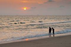 站立在海滩的两个人剪影  免版税库存图片