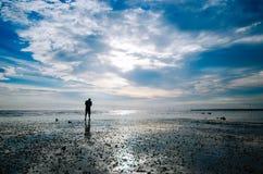 站立在海滩的人剪影 库存照片