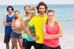 站立在海滩的体育衣物的朋友 库存图片