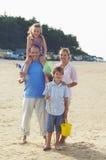 站立在海滩的假期的家庭 库存照片
