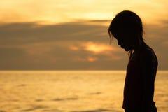 站立在海滩的哀伤的白肤金发的小女孩画象  免版税库存图片