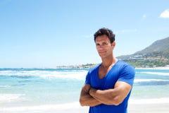 站立在海滩的坚固性俊男 免版税库存图片