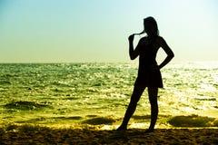 站立在海滩的夏天礼服的亚洲少妇 免版税库存图片