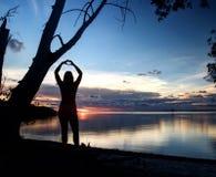 站立在海滩的女孩塑造心脏用她的手 免版税库存照片