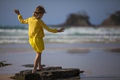 站立在海滩的女孩 免版税库存图片