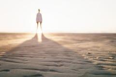 站立在海滩的女孩Defocused照片 库存照片