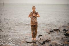站立在海滩的妇女一个感恩的namaste瑜伽姿势在多云天气的海洋旁边 禅宗,凝思,和平 免版税库存照片