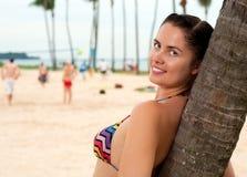 站立在海滩的妇女近的棕榈树 免版税库存照片