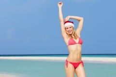 站立在海滩的妇女戴圣诞老人帽子 免版税图库摄影