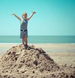 站立在海滩的小山的小男孩孩子与他的胳膊 免版税库存照片