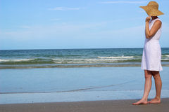 站立在海滩的帽子的妇女看海洋 免版税库存图片