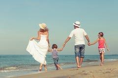 站立在海滩的愉快的家庭在天时间 库存照片