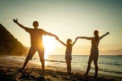 站立在海滩的愉快的家庭 免版税库存图片