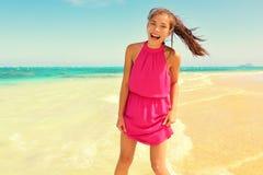 站立在海滩的桃红色礼服的愉快的少妇 库存图片
