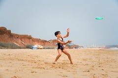 站立在海滩的泳装的逗人喜爱的youg女孩在投掷一个绿色圆盘的海旁边 免版税库存图片