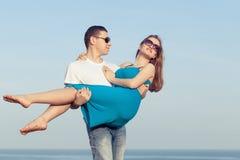 站立在海滩的爱恋的夫妇在天时间 免版税库存图片