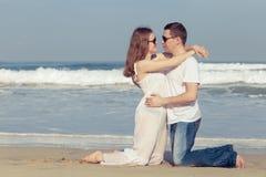 站立在海滩的爱恋的夫妇在天时间 图库摄影