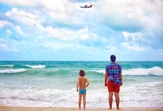 站立在海滩的父亲和儿子在多暴风雨的天气,观看平面飞行 免版税库存图片
