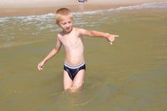 站立在海水的男孩 图库摄影