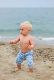 站立在海滩的白肤金发的婴孩 免版税库存图片