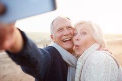 站立在海滩的资深夫妇采取Selfie 免版税库存照片