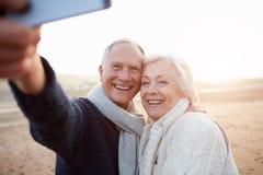 站立在海滩的资深夫妇采取Selfie 免版税库存图片