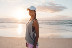 站立在海滩的运动服的适合的少妇 免版税库存照片
