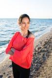站立在海滩的年轻人微笑的可爱的妇女的画象,当休息在训练的健身以后户外时 免版税库存图片