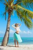 站立在海滩的年轻愉快的妇女在棕榈树下 免版税库存照片