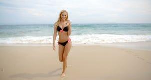 站立在海滩的黑比基尼泳装的白肤金发的妇女