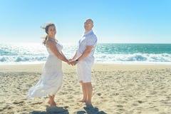 站立在海滩的年轻浪漫夫妇握手 库存图片