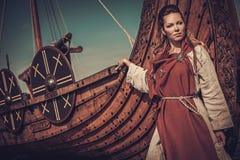 站立在海滨的Drakkar附近的北欧海盗妇女 免版税库存图片