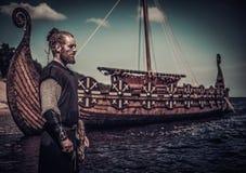 站立在海滨的Drakkar附近的北欧海盗战士 免版税库存图片