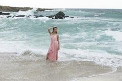 站立在海洋碰撞的波浪的桃红色礼服的妇女  免版税库存图片