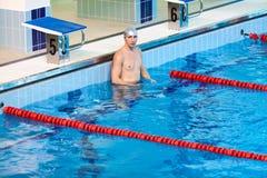 站立在游泳池中水的游泳者  免版税库存图片