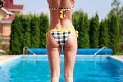 站立在游泳池旁边的比基尼泳装的女孩,准备跃迁 免版税库存照片