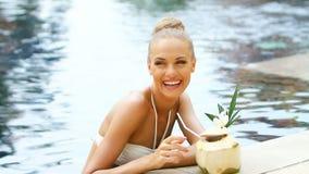 站立在游泳池的可爱的白肤金发的妇女 股票视频