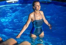 站立在游泳池的轻松的健康妇女 库存图片