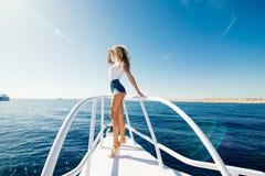 站立在游艇一个晴朗的夏日,微风开发的头发,背景的美丽的海的鼻子的妇女 库存照片